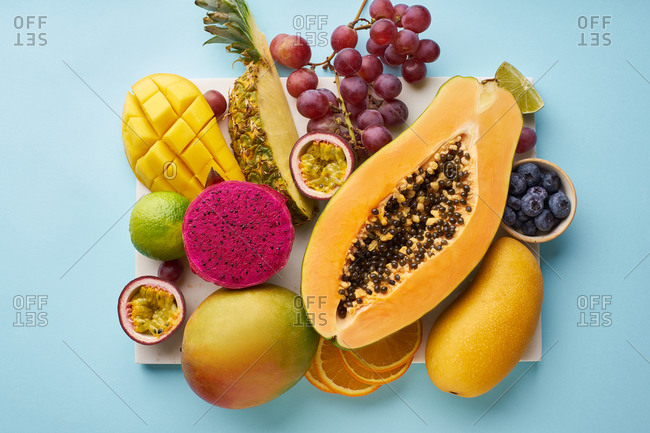 Top view of flat lay with tropical fruits on a tray: papaya, mango, dragon fruit and pineapple on blue background. Summer treat