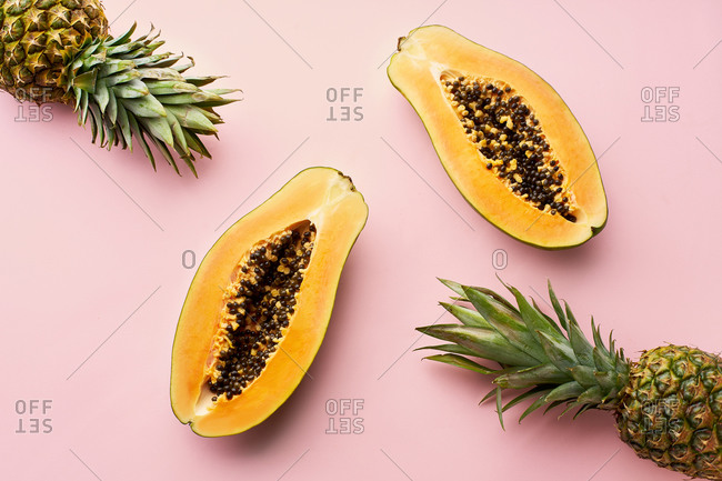 Top view of flat lay with sliced papaya and pineapple on pink background. Tropical fruits.