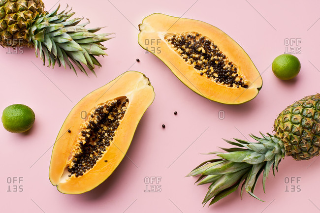 Top view of flat lay with summer tropical fruits: papaya, lime and pineapple on pink background