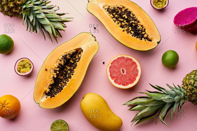 Top view creative layout with exotic summer fruits: papaya, pineapple, lime, yellow mango and passion fruit on pink background