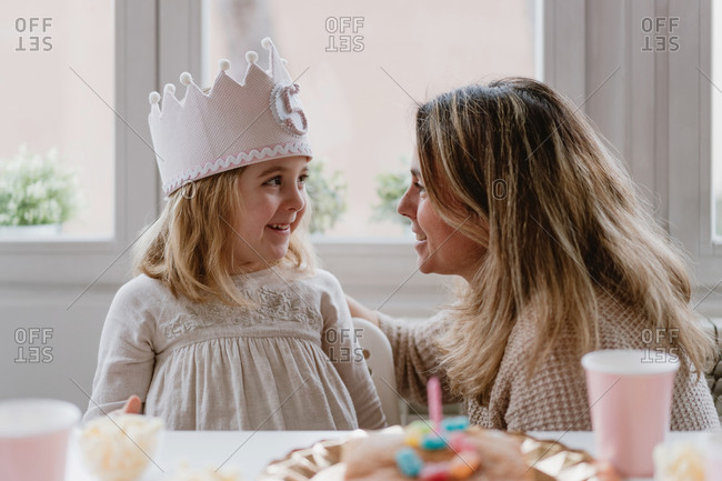 Side view of cheerful mother placing felt handmade crown on daughter while celebrating birthday together at home