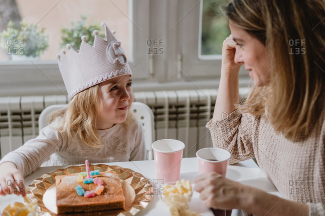 Positive mother in casual clothes sitting at wooden table and talking with kids celebrating birthday at home