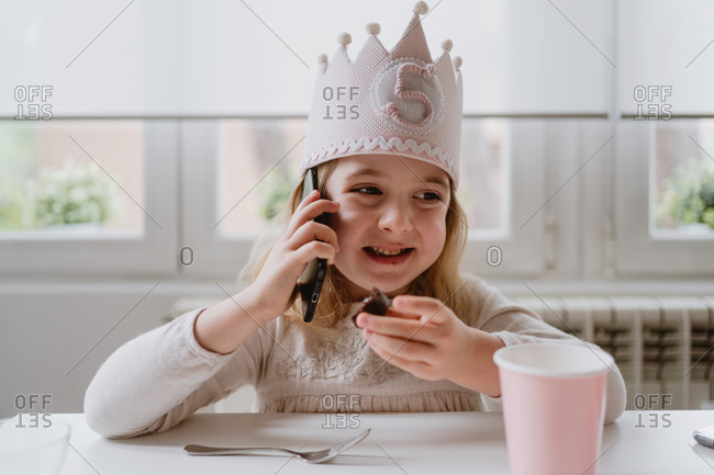 Happy little girl in casual clothes and holiday crown sitting at table and talking on smartphone while eating sweet candy during birthday party at home