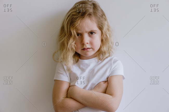 Disappointed little child in casual t shirt looking at camera on white background in studio
