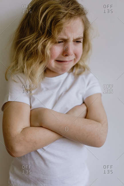 Naughty kid with wavy hair in casual clothing standing with folded arms and weeping with closed eyes on white background