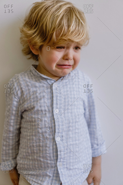 Disappointed little child in casual shirt standing near white wall and weeping on white background in studio