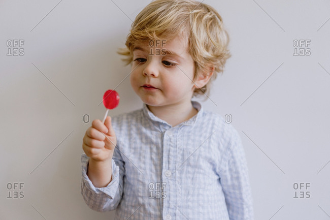 Adorable toddler with blond hair enjoying tasty red lollipop while standing against gray wall