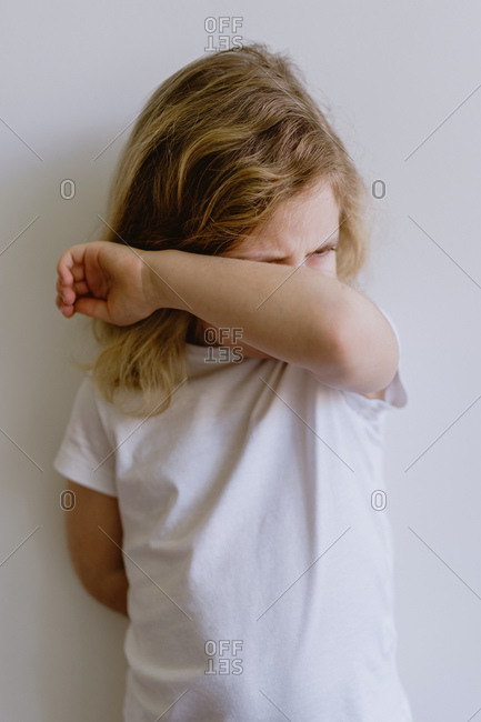 Naughty kid with wavy hair in casual clothing standing with folded arms and weeping looking away on white background