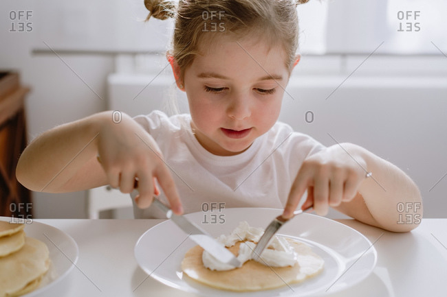 Thrilled little child in casual t shirt sitting at table with plate of tasty pancake garnished with heart shaped whipped cream