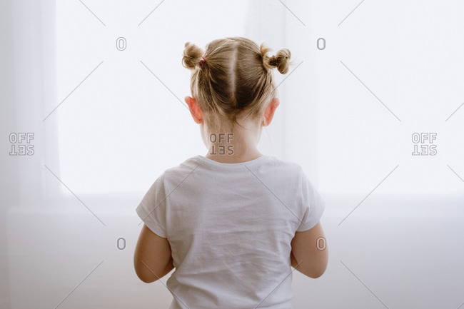 Back view of unrecognizable depressed little kid in casual outfit standing in bright apartment