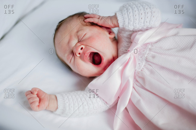 High angle of adorable baby girl in cozy dress lying in cot and yawning while sleeping