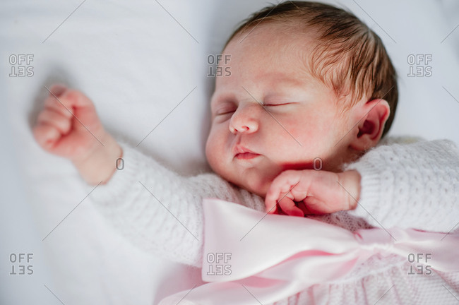High angle of adorable baby girl in cozy dress lying in cot while sleeping