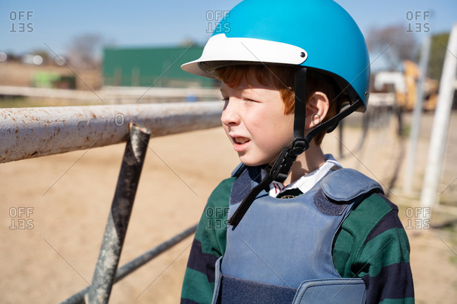 Preteen equestrian in protective helmet for horseback riding standing near metal fence on sunny day and looking away