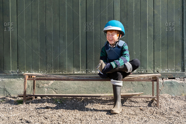 Smiling boy in protective helmet sitting on wooden bench of outdoors arena and preparing for horseback riding while putting on boots with closed eyes