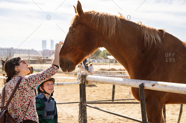 Cheerful woman in casual wear and preteen equestrian in protective helmet standing on sandy arena near fence and caressing chestnut horse
