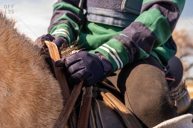 Crop preteen jockey in protective equipment riding dun horse during lesson in equestrian school