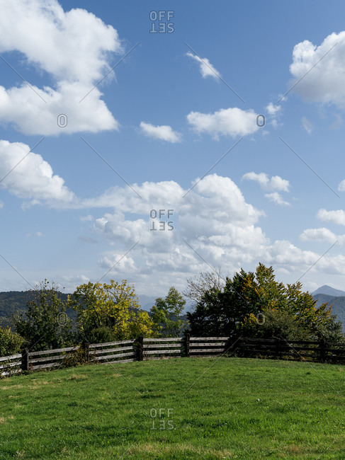 Amazing scenery of mountainous area with lush meadow surrounded by wooden barrier under blue sky in summer