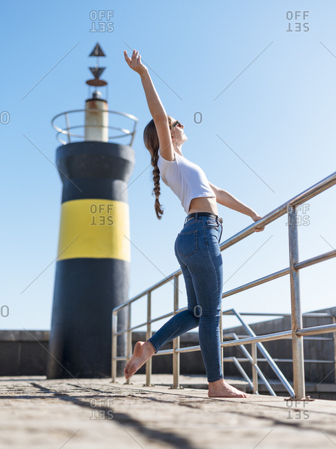 Low angle side view of dreamy female in casual wear standing barefoot on stone embankment on background of lighthouse and enjoying sunlight