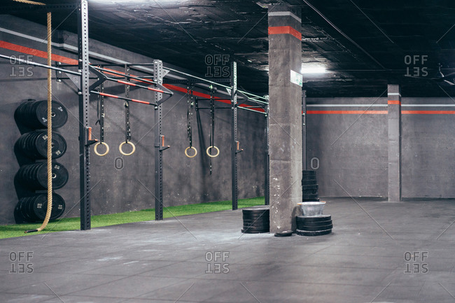Loft interior of sports hall with gymnastic rings and weight plates stacked on concrete floor