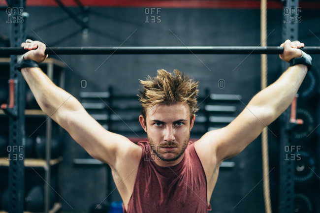 Strong male athlete doing exercises with barbell while working out in modern gym and looking at camera