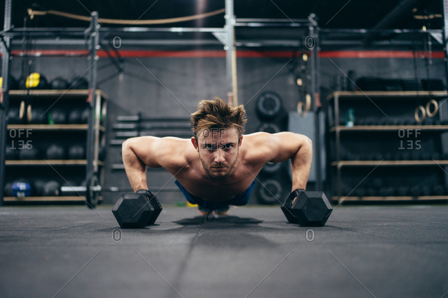 Powerful shirtless male athlete doing push ups and using dumbbells while training in gym and looking at camera