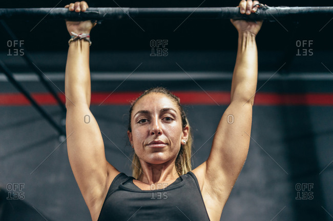 Serious sweaty muscular sportswoman perform pull-ups in gym looking at camera