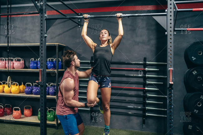 Serious sweaty muscular sportswoman with instructor helping to perform pull-ups in gym looking away