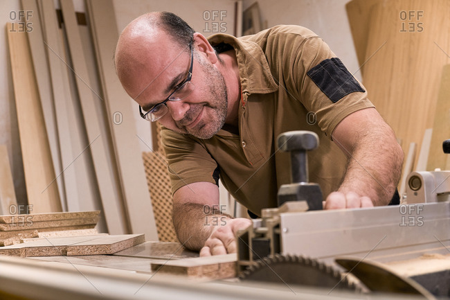 Carpentry master in glasses and casual clothes measuring and sawing timber while crafting detail using electric trimming machine in light contemporary workshop
