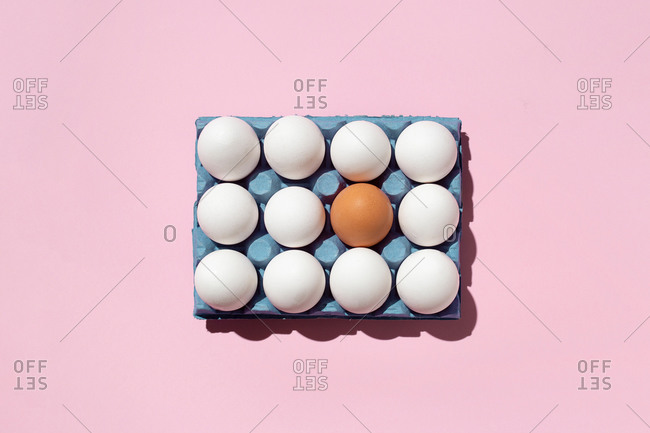 Top view of seamless background of brown and white eggs placed on pink surface in studio