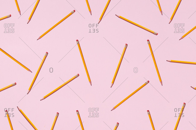 Top view of seamless background of pencils chaotically scattered on pink surface