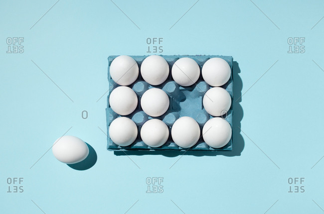 Top view of white eggs placed in paper tray demonstrating concept of difference on blue background in studio
