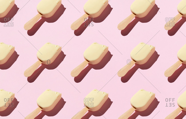 From above of pattern of popsicles placed in rows on pink background in studio