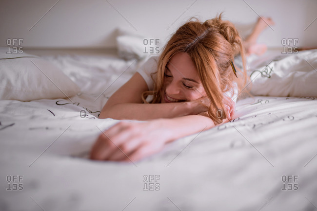 Young satisfied female with pencil in red hair having rest after awakening at weekend morning and home lying on stomach on cozy bed with white linen and smiling with closed eyes