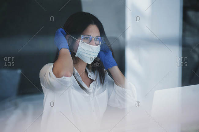 Serious female in latex gloves putting on protective medical mask while standing near window at home during coronavirus outbreak