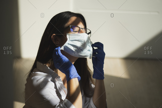 Serious female with closed eyes in latex gloves putting on protective medical mask while standing at home during coronavirus outbreak