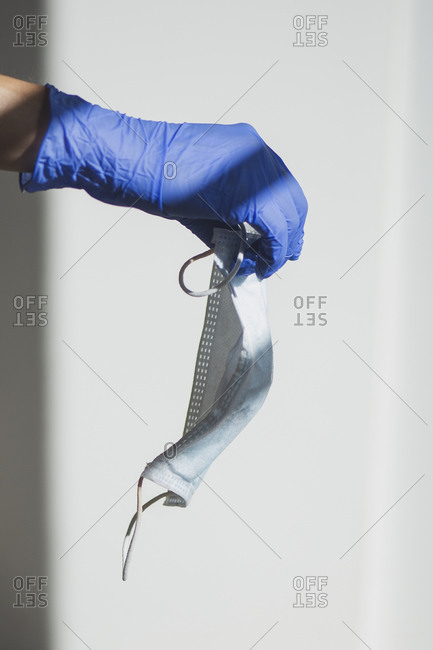 Crop anonymous person in blue latex glove holding medical mask against white background representing concept of coronavirus protection and prevention