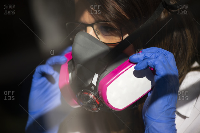 Closeup of crop anonymous female wearing professional respirator mask for coronavirus prevention
