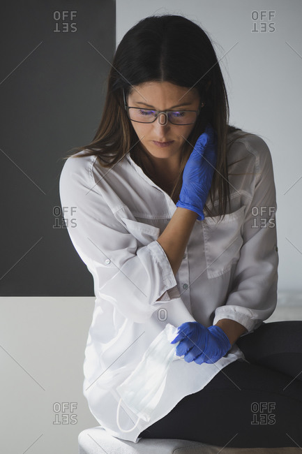 Modern young female in casual white blouse and protective latex gloves holding disposable medical mask