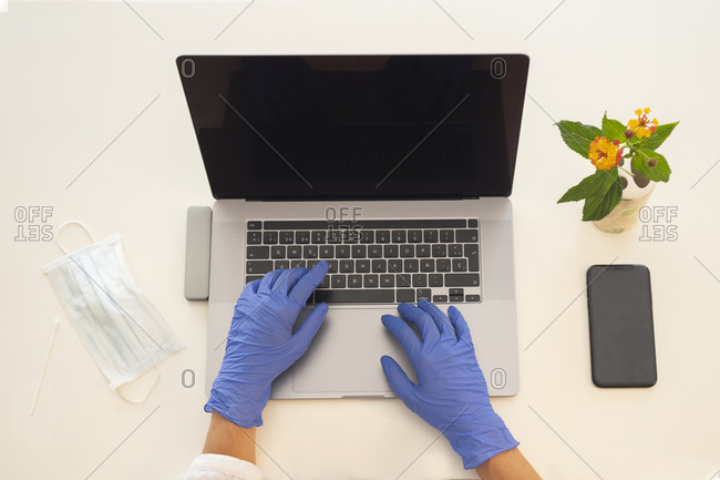 From above of crop anonymous female in latex gloves typing on laptop keyboard at workplace with protective mask placed nearby during coronavirus quarantine