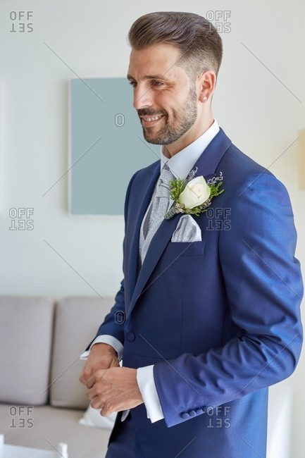 Smiling fiance in classy suit standing in bright living room of modern apartment during wedding fees