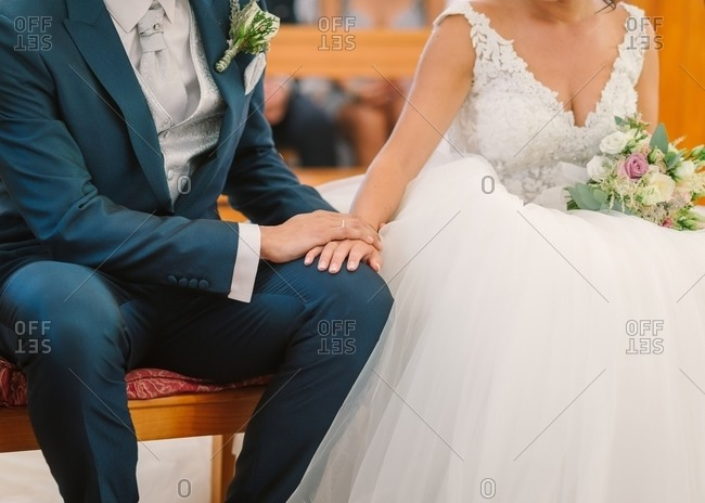 Unrecognizable groom in elegant suit with boutonniere and bride in white wedding gown sitting on bench and holding hands during ceremony in church