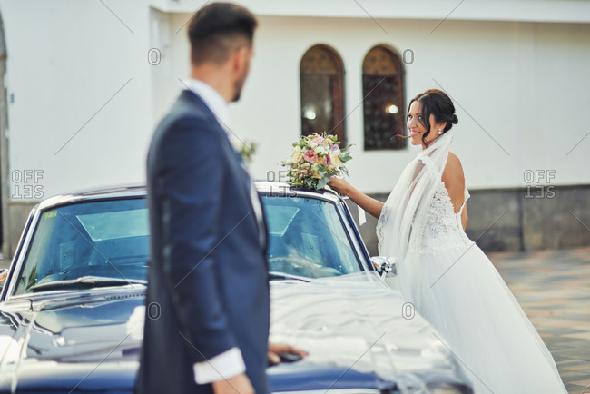 Side view of smiling bride wearing elegant wedding dress and veil standing with bouquet near luxury automobile and looking at groom in elegant suit