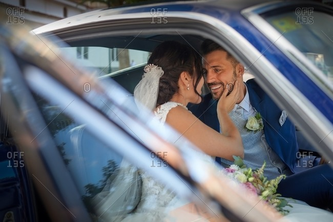 Happy bride in wedding dress and groom in classy suit sitting in vintage automobile and looking at each other
