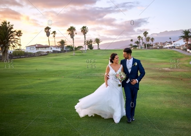 Cheerful groom in elegant suit and bride in white wedding dresses cuddling and walking on lawn while looking at each other during wedding celebration