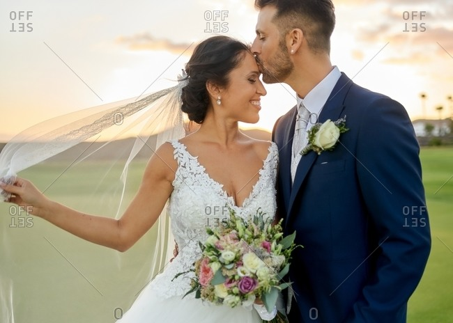 cheerful groom in elegant tuxedo lifting bride in wedding gown while standing on tropical green coast in evening time