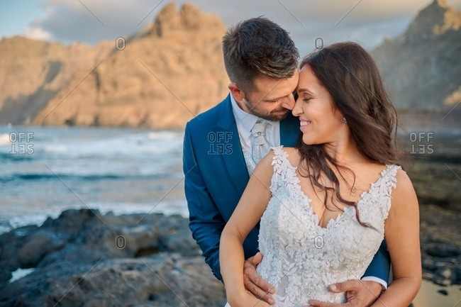 Tender bride in elegant wedding dress and groom in classy suit hugging with closed eyes while standing together at seashore with mountains during sunset