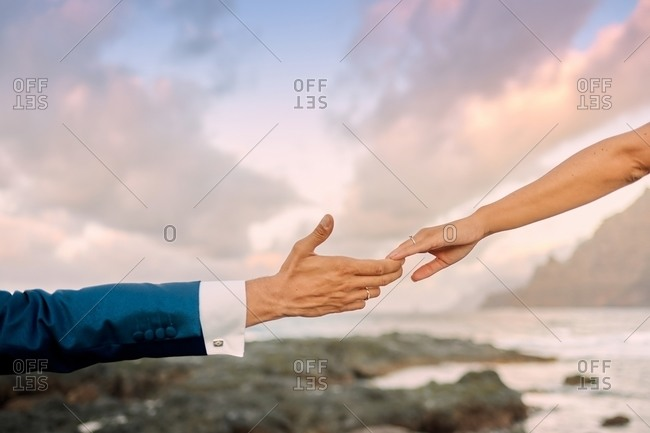 Unrecognizable groom in elegant suit and bride gently touching fingers while standing on rocky coast during magnificent sunset