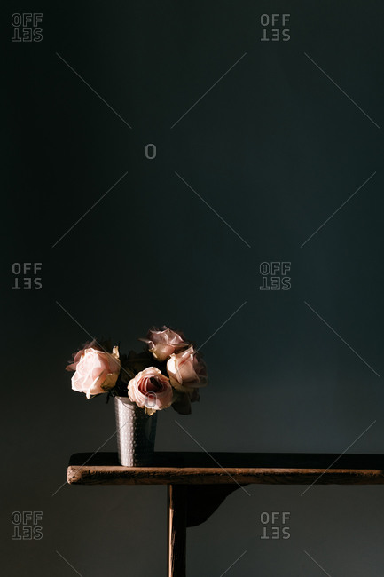 Blooming fresh pink roses in vintage vase placed on wooden table at black wall in modern apartment