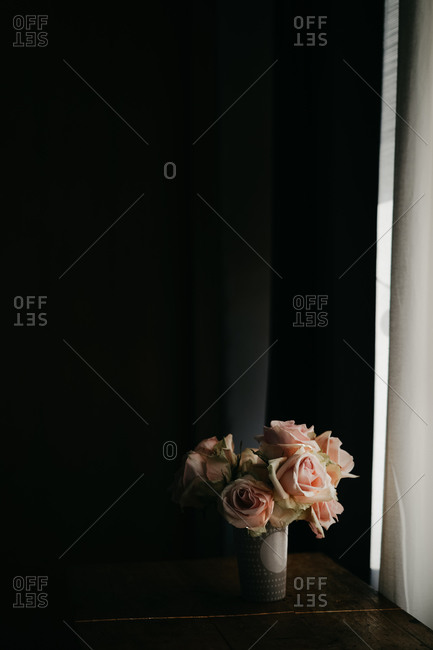 Blooming fresh pink roses in vintage vase placed on wooden table at black wall near windows in modern apartment