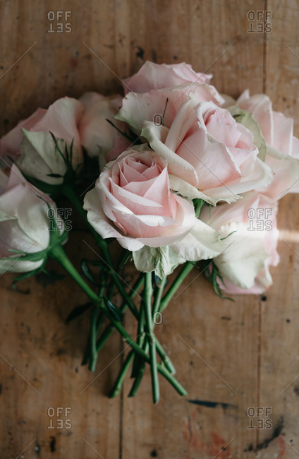 Top view of bunch of fresh pink roses placed on shabby wooden table in light room